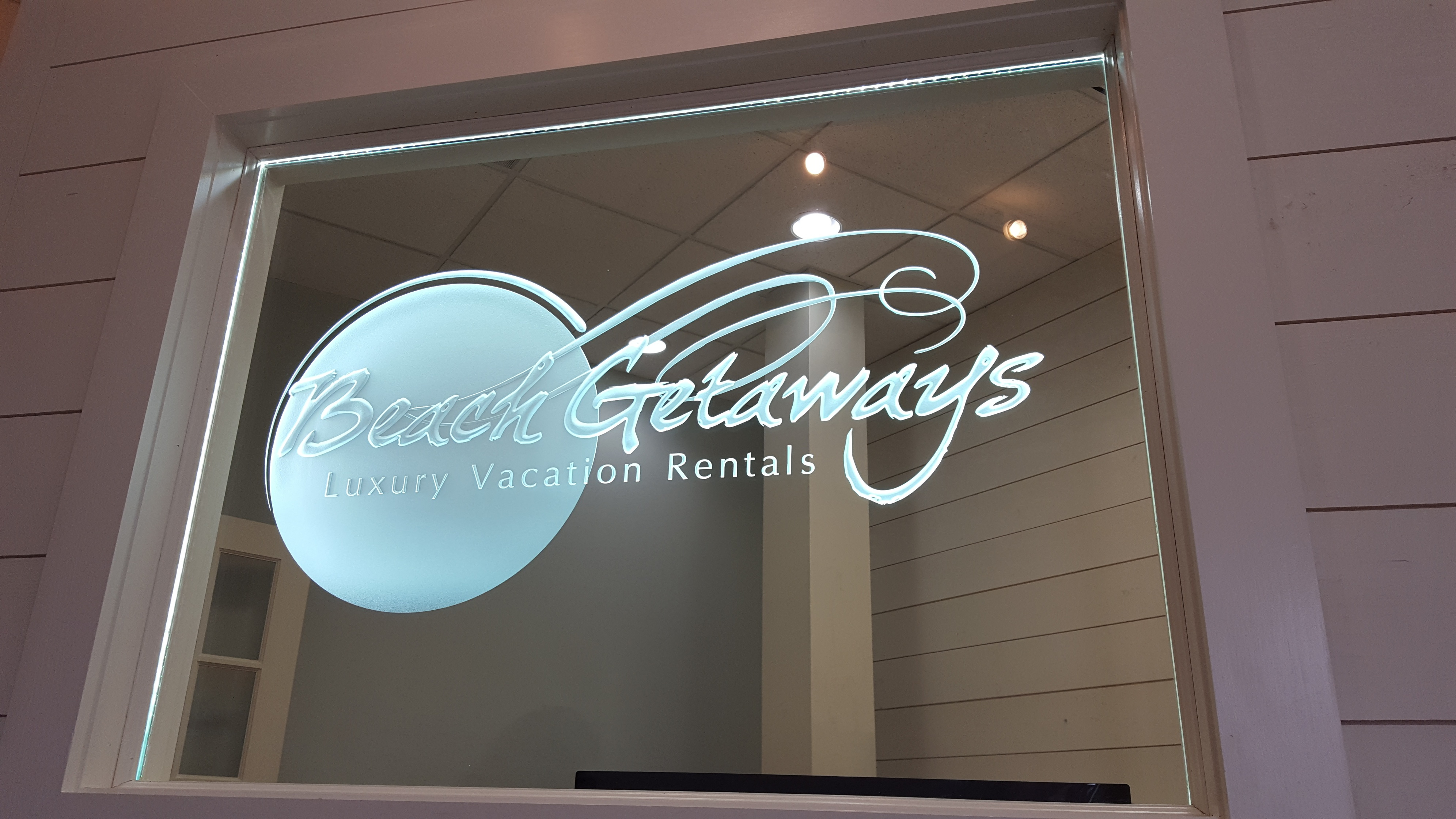 Beach Getaways  Luxury Vacation Rentals logo sandblasted on glass by Glass Graphics