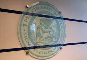 Fraternity seal sandblasted sign on stand-off mounting by Glass Graphics of Atlanta.